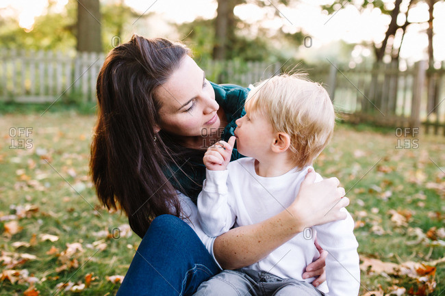 Portrait of woman and son sitting in backyard in autumn