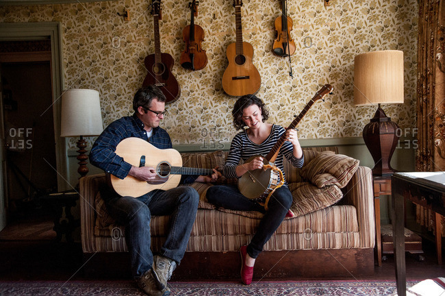 Shelter Island, Long Island, New York, USA - April 6, 2013: Husband and wife practicing songs on their guitar and banjo