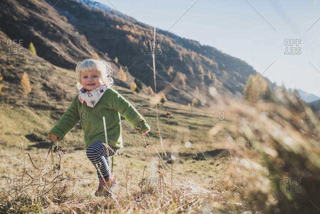 Little girl playing in a mountain valley