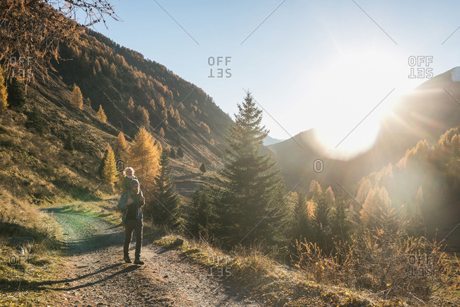 Father and daughter hiking on dirt road through mountains
