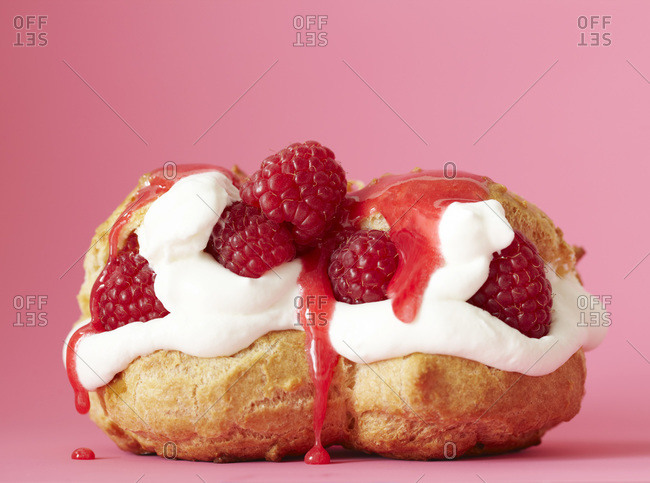 Raspberry eclairs stuffed with cream and fresh fruit