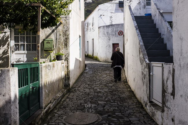 Woman walking in Corvo village. Azores, Portugal