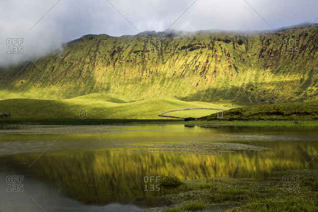 Caldeirao edge reflected on a lagoon, Corvo Island, Azores, Portugal