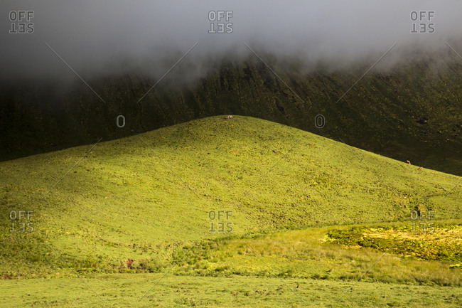 Low clouds over a hill inside Caldeirao, Corvo Island, Azores, Portugal