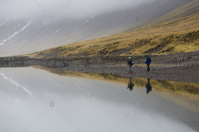 Men walking on banks of Icelandic lake