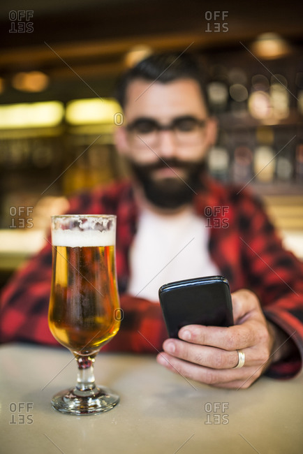 Bearded man sitting in bar checking emails with beer on counter