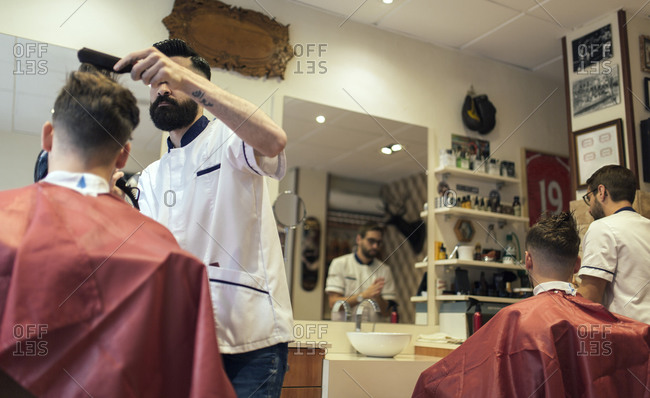 Two barbers cutting hair of twin brothers in barber shop