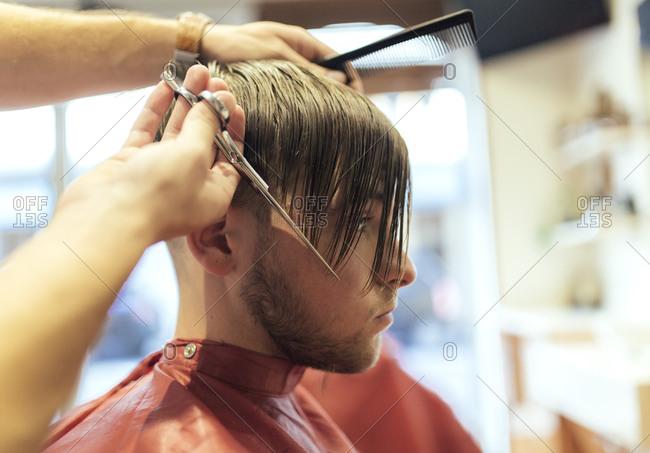 Barber cutting wet hair of a customer