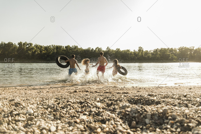 Friends with inner tubes running in river