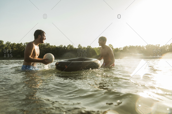 Two friends with inner tube and ball in water