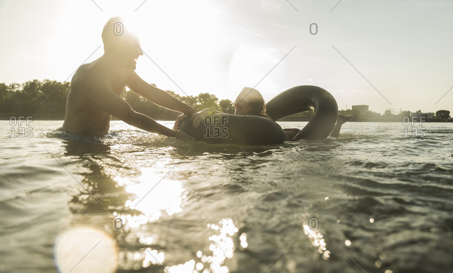 Happy couple with inner tube in water