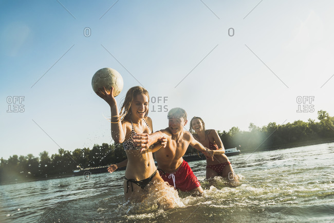Young woman keeping a ball away from friends in water