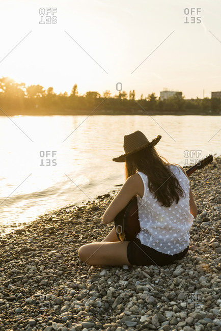 Back view of a young woman playing guitar at the riverside at sunset