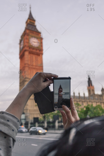 Woman taking photo of Big Ben with her smartphone