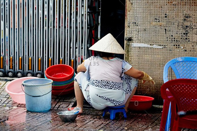 Asian woman washing bowls in the street