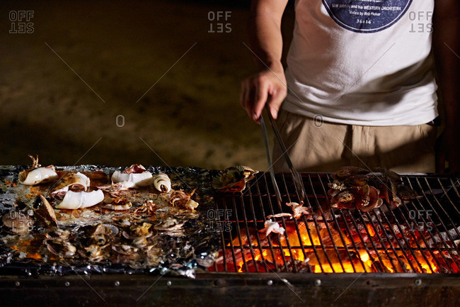 Man barbequing seafood on a large grill