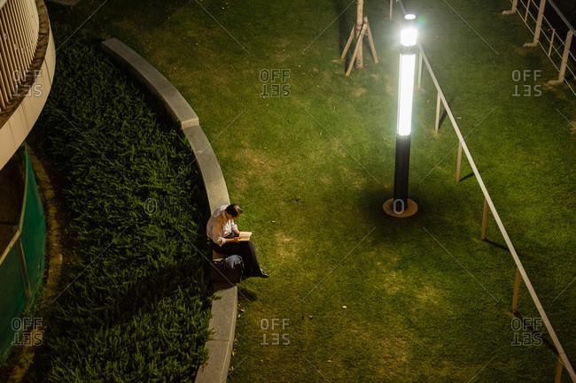 Man sitting in Nakanoshima park at night reading in Osaka, Japan