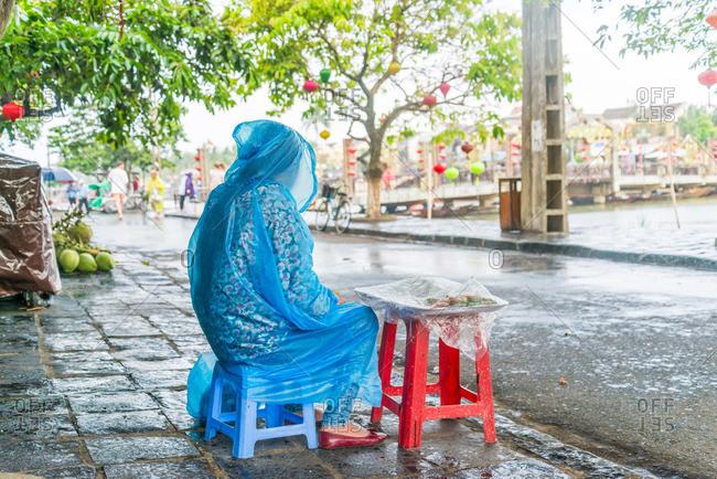 Vietnamese street vendor sitting in the rain