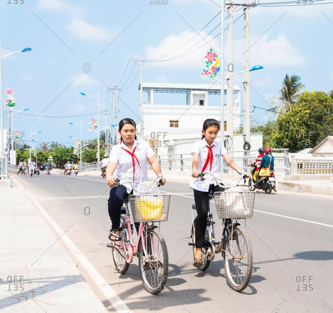 Duong Dong, Phu Quoc Island, Vietnam - April 17, 2015: Vietnamese schoolgirls riding their bikes to school