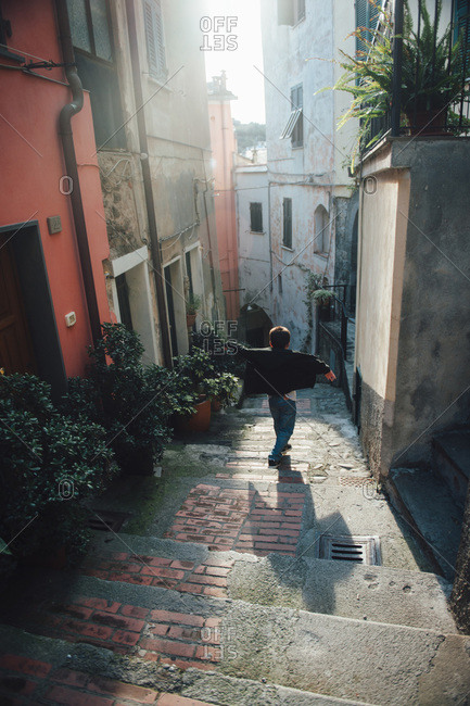 Little boy walking between buildings in a village in Cinque Terre, Italy