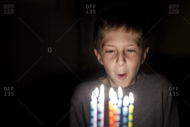 Boy blowing out birthday cake candles