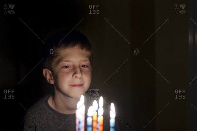 Boy making a wish with birthday cake candles