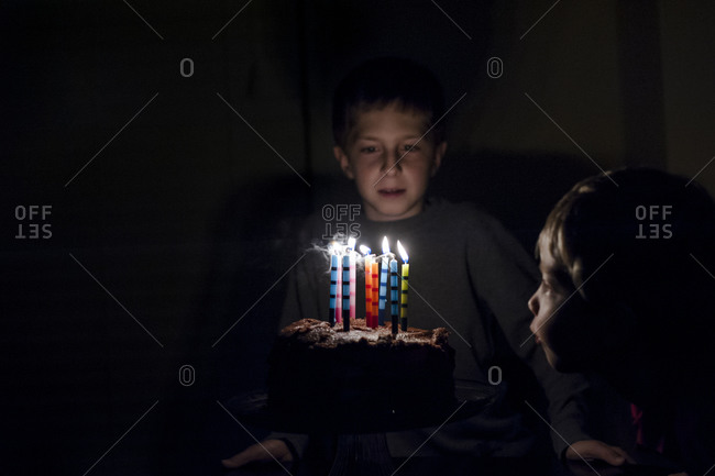 Boys trying to blow out candles on birthday cake