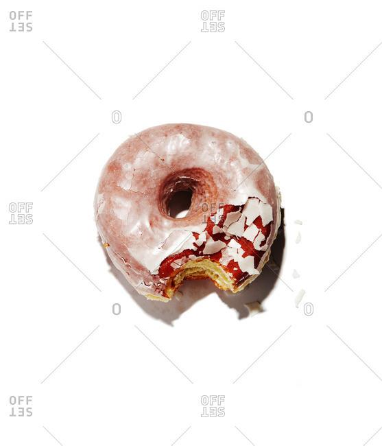 Glazed doughnut on a white background missing a bite