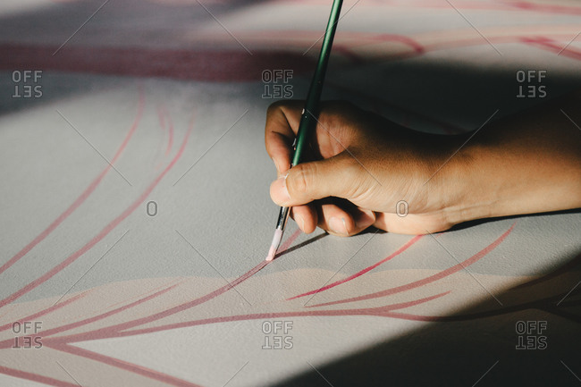 Close-up of artist's hand painting pink lines on canvas