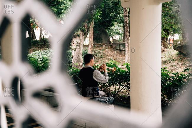 View through screen of man playing trumpet in garden