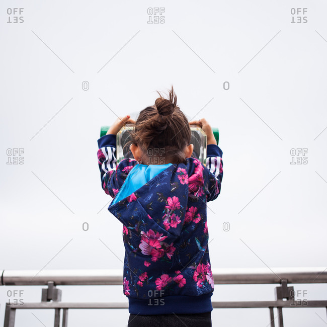 Back view of young girl looking through coin operated binoculars