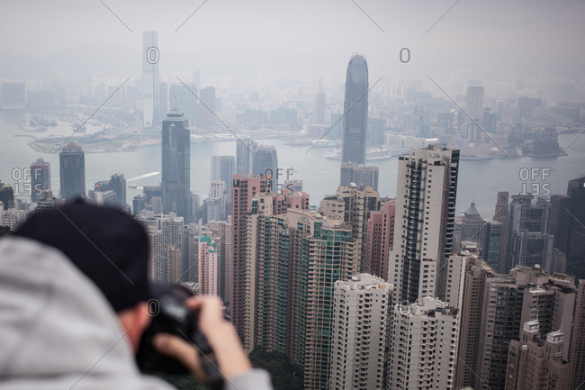 Back view of photographer taking picture of Hong Kong skyline