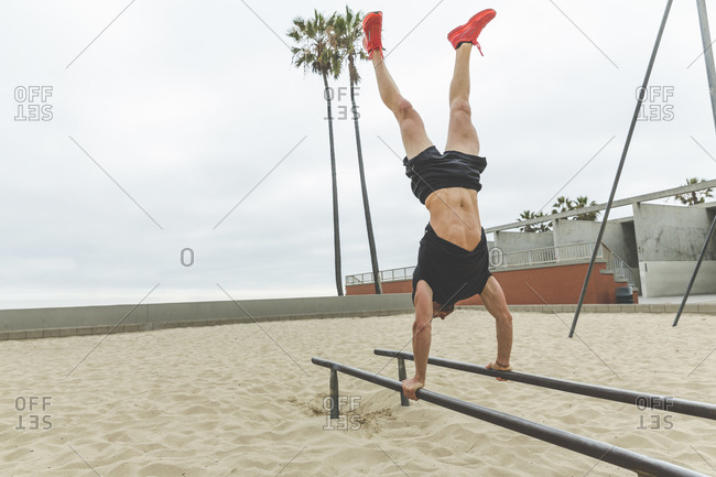Athletic man doing a handstand during a beach workout
