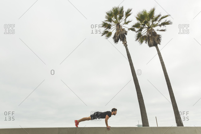 Athletic man doing push ups on a wall