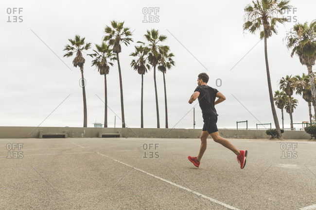Athletic man running next to a building during an outdoor workout