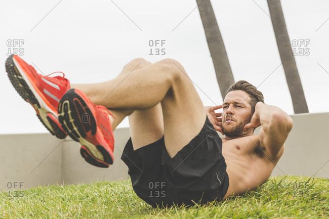 Shirtless athletic man doing crunches during an outdoor workout