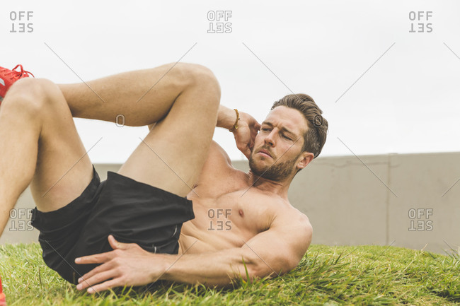 Shirtless athletic man doing a crunch twist during an outdoor workout