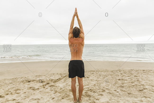 Shirtless athletic man standing with hands touching in the air