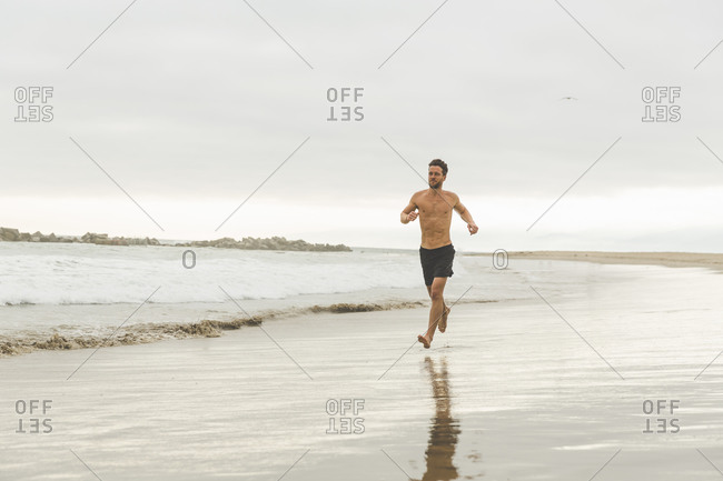 Shirtless athletic man running barefoot on the beach