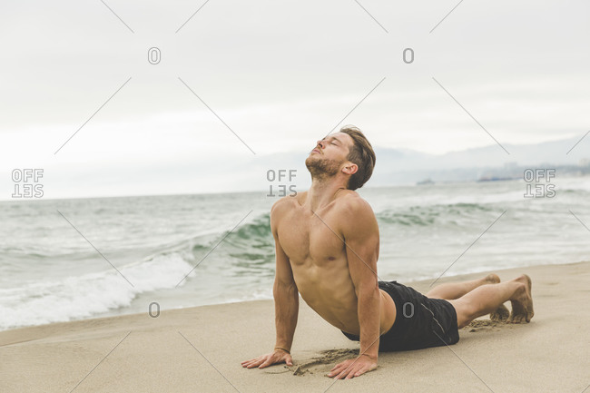 Shirtless athletic man stretching on the beach