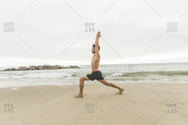 Shirtless athletic man doing yoga positions on the beach