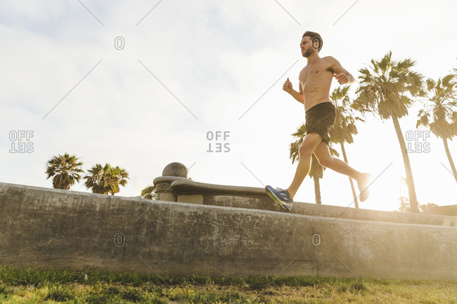 Shirtless man running along a cement wall