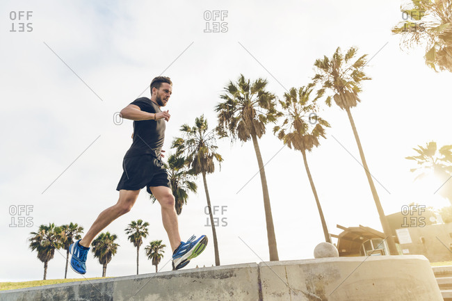 Man running along a cement wall
