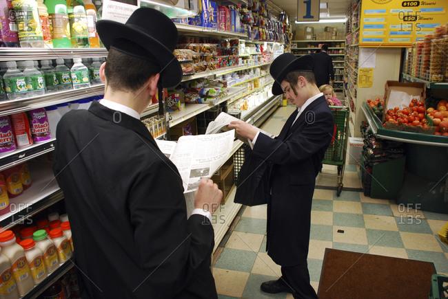 Kiryas Joel, New York - November 30, 2006: Young Hassidic men read newspapers in a store