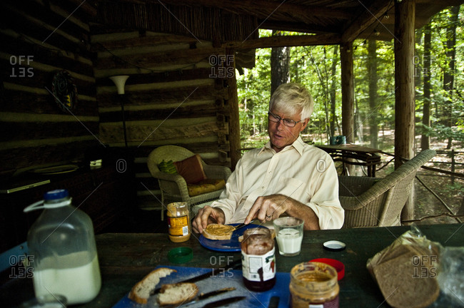 Chapel Hill, North Carolina - September 28, 2010: Sculptor Patrick Dougherty on his screened porch with sandwiches
