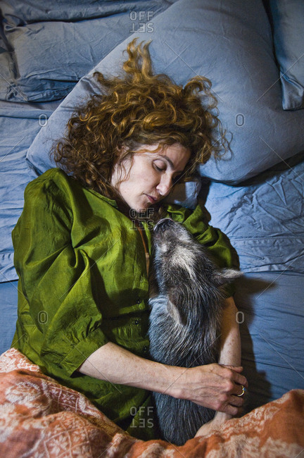 Mt. Tremper, New York - February 11, 2011: Artist Kathy Ruttenberg sleeping with her pot belly pig
