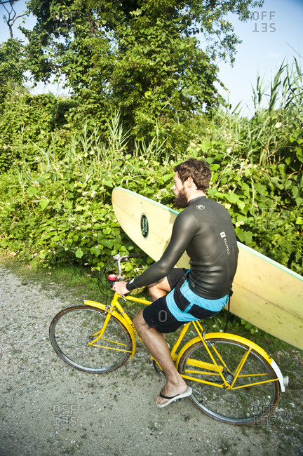 Montauk, New York - July 23, 2011: Surfer carrying his board while riding a bike
