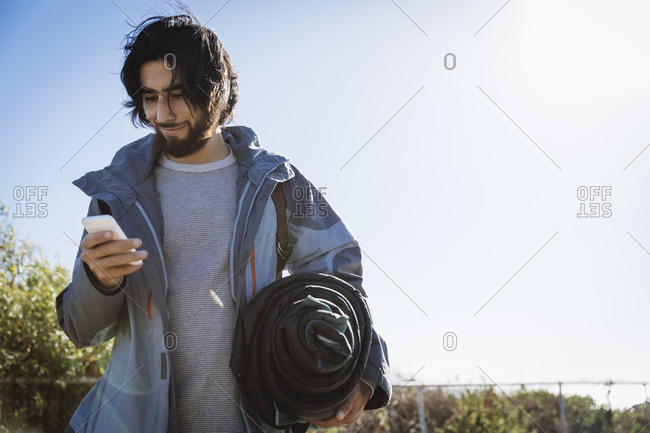 Young man carrying a sleeping bag and looking at his phone