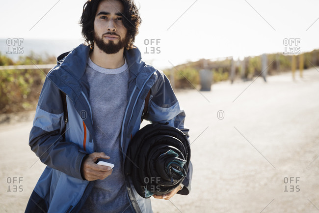Young man carrying a sleeping bag and cell phone