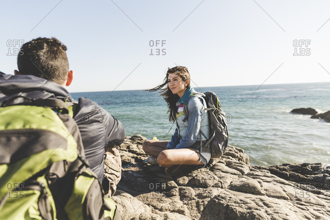 Backpacking couple sitting by the ocean
